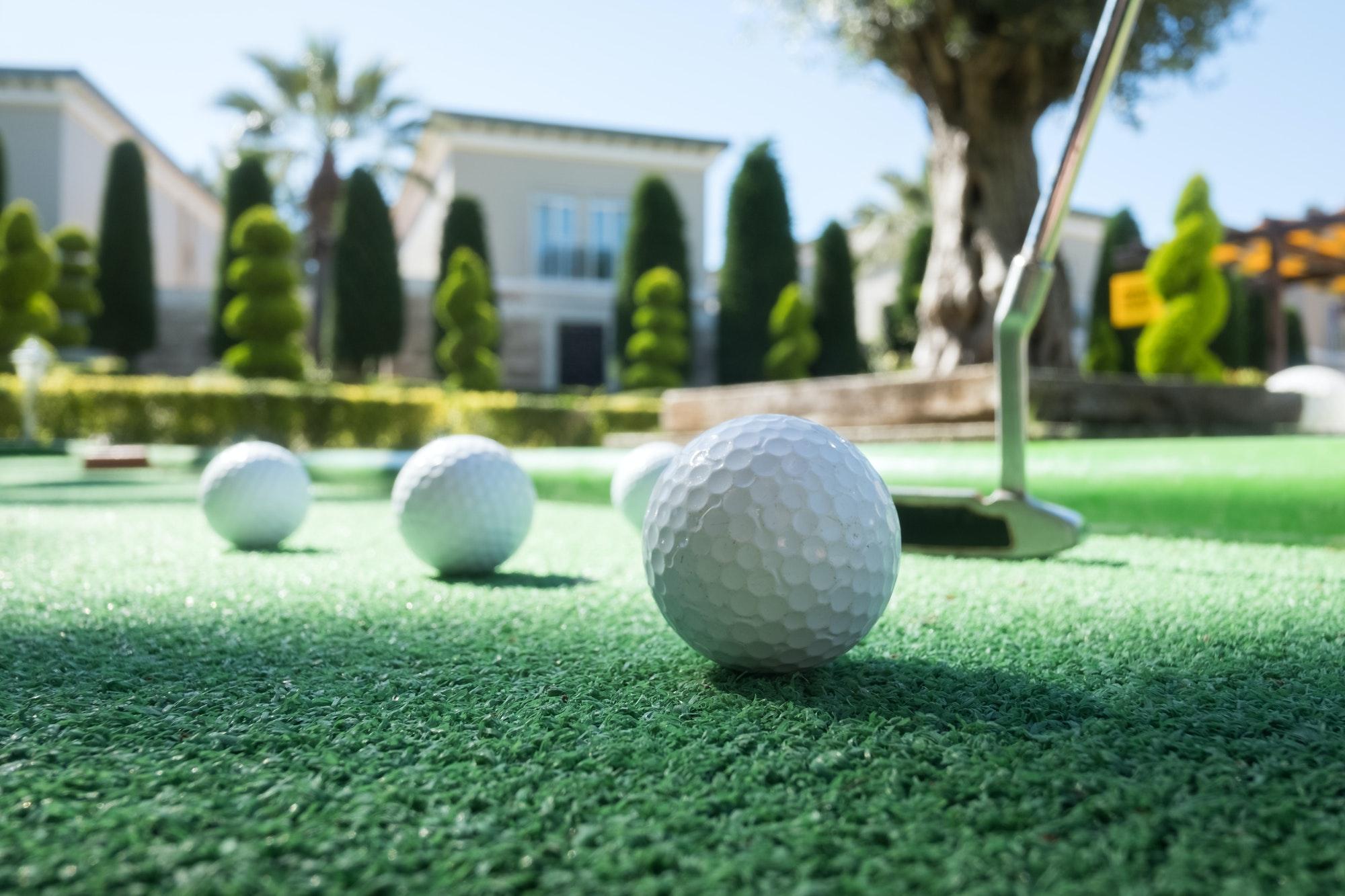 Instalación de Césped Artificial artificial grass hotel Mini golf scene with ball and club